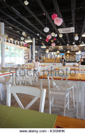 Wooden tables with white chairs and decoration on the ceiling in the Rusalka restaurant on August 2017 in Poznan, - Stock Photo