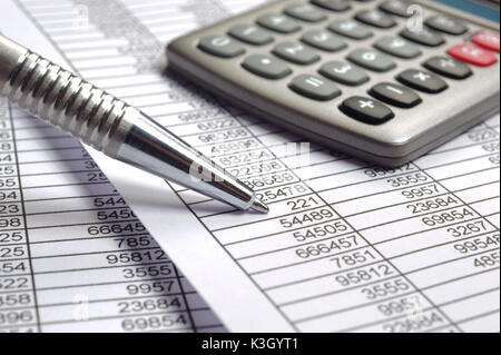 Electronic calculators and ballpoint pens lie on a number table - Stock Photo
