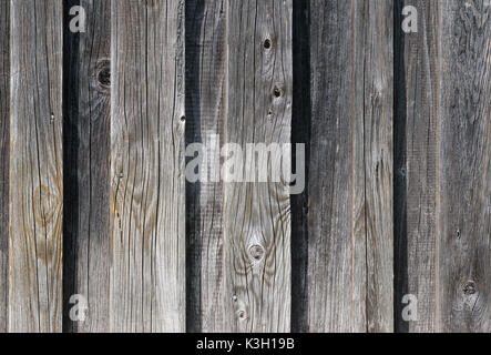 Weathered old wooden wall detail. Simple gray boards with knotholes and coarse grain nailed together. Outdoor. Backgrounds. - Stock Photo