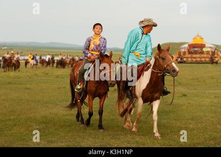Inner Mongolia, China-July 25, 2017: Horsemen riding horses in grasslands of Inner Mongolia.The horses are very - Stock Photo