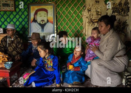 Inner Mongolia, China-July 26, 2017: Traditionally dressed Mongolian family sitting in their tent (called as Yurt). - Stock Photo