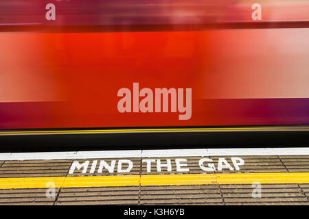 England, London, The Underground, Mind the Gap Sign and Moving Train - Stock Photo