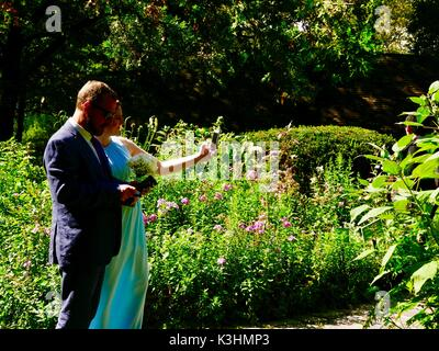 Couple, members of wedding party in fancy clothes, taking selfie in garden. Central Park, Manhattan, New York, NY, - Stock Photo