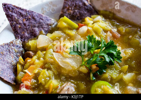 Closeup on Mexican chili pepper stew in tan bowl decorated with blue corn tortillas on white tablecloth served with - Stock Photo