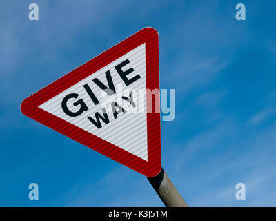 Give Way road sign set against a blue sky - Stock Photo