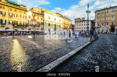 Late afternoon on the Piazza Navona as the sunlight shines off a window and locals and tourists enjoy themselves - Stock Photo