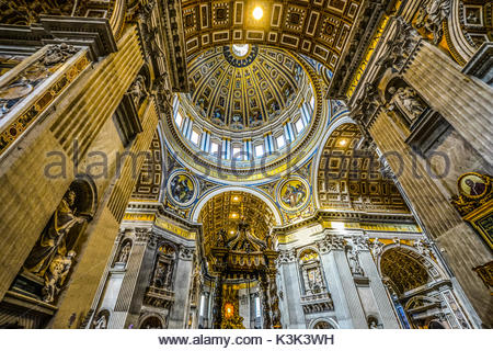 The Cupola of St Peters Basilica in Vatican City, Rome with brilliant gold and blue highlighting the ceiling - Stock Photo