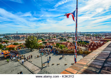 City view and skyline from atop the Prague Castle Complex with tourists below and a Czech flag flying on a flagpole - Stock Photo