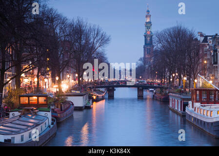 Netherlands, Amsterdam, along Prinsengracht canal, towards Westerkerk church dusk - Stock Photo