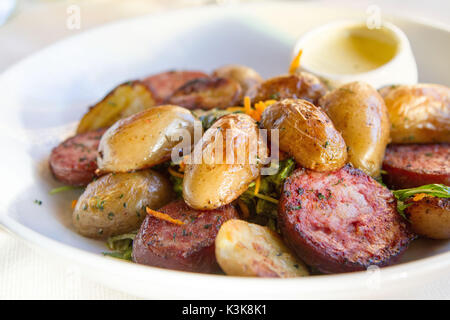 Slices of Jesu de Morteau on a bed of salad served with cancoillote cheese, local specialty of Doubs from the region - Stock Photo