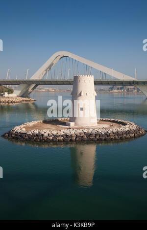 UAE, Abu Dhabi, Sheikh Zayed Bridge, designed by Zaha Hadid and old Al Maqta Fort watchtower - Stock Photo