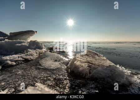 The rising sun is reflected on the ice by the Bodden of the German Baltic Sea with Rügen. In the foreground stacked - Stock Photo