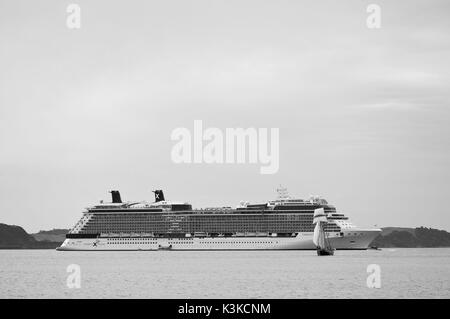 Small sailing ship in front of big cruiser in New Zealand. - Stock Photo