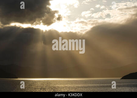 Sunrays break through the thick cloud cover on the north coast of the south island of New Zealand and makes the - Stock Photo