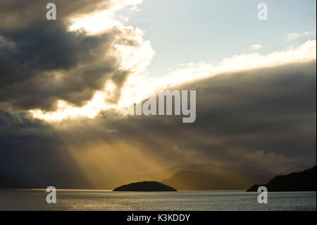 Sunrays break through a thick cloud cover over the sea and illuminated a small island and in the background fjords - Stock Photo