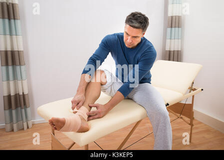Man Sitting On Bed Typing Elastic Bandage To His Foot - Stock Photo