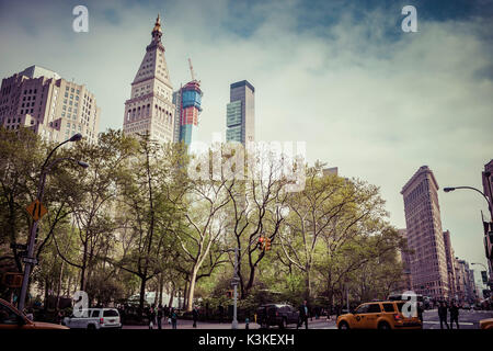 Typical NY Streetscape, people and cars at 5th Ave, Flatiron Building, Manhatten, New York, USA - Stock Photo