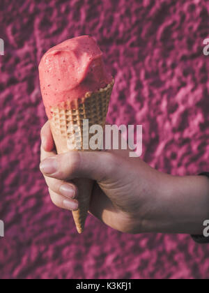Hand of a boy holding a strawberry ice cream cone on a pink background - Stock Photo