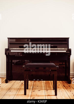 Black piano with a piano stool on a wooden ground in the living room - copy space - Stock Photo