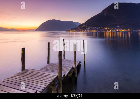 A pier in Sulzano, in front of Montisola and Peschiera Maraglio town during a winter sunset, Brescia Province, Iseo - Stock Photo