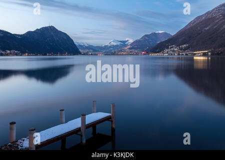 Lugano lights turns on after sunset, Riva San Vitale, Lake Ceresio, Canton Ticino, Switzerland. - Stock Photo