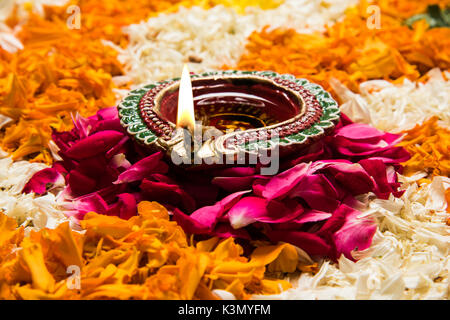 flower rangoli for Diwali or pongal or onam made using marigold or zendu flowers and red rose petals over white - Stock Photo