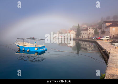 Perast is an old town on the Bay of Kotor in Montenegro. In the picture a foggy morning on the bay with a little - Stock Photo