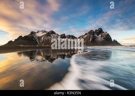 Stokksnes, Hofn, East Iceland, Iceland. Vestrahorn mountain reflected on the shore at sunset. - Stock Photo