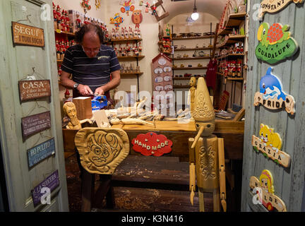 Local artist making wooden souvenirs in Rome, Italy - Stock Photo