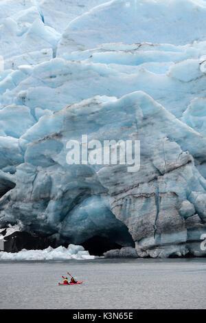 Red canoe (kayak) close to glacier front, Portage glacier, Alaska,USA - Stock Photo