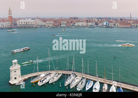 Europe, Italy, Veneto, island of San Giorgio Maggiore. One of the headlights of the dock and some moored boats, - Stock Photo