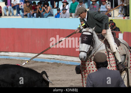 June 18, 2017 Pujili, Ecuador: picador on horseback redy to pierce the back of the bull with lance - Stock Photo