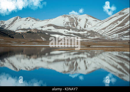 Reflections on Piano Grande in a winter day, Piano Grande di Castelluccio di Norcia, Monti Sibillini NP, Italy - Stock Photo