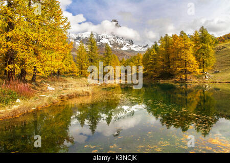 The Matterhorn stands out among the clouds and it is reflected in the small lake Blu surrounded by colorful trees - Stock Photo