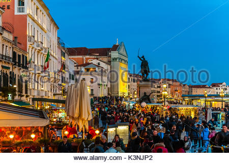 Promenade on Riva degli Schiavoni on the waterfront near Piazza San Marco is crowded with revelers during the Venice - Stock Photo