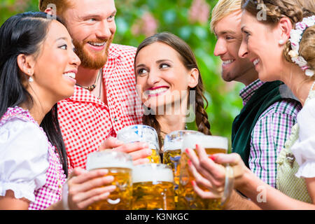 Friends having fun in beer garden while clinking glasses - Stock Photo