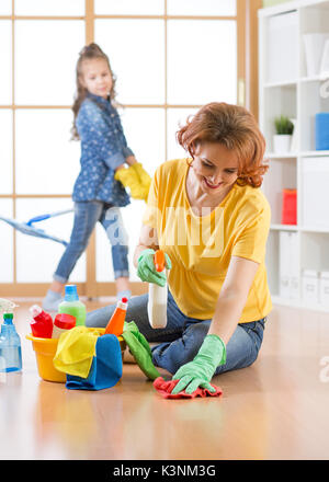 Happy family cleans the room. Mother and her daughter do the cleaning in the house. - Stock Photo
