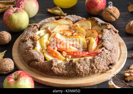 Apple Galette. Healthy homemade wholegrain fruit pie (galette) with organic apples, walnuts, cinnamon and brown - Stock Photo