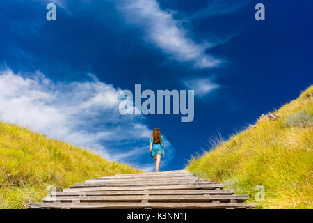 Young woman climbing stairs outdoors in an idyllic travel destin - Stock Photo