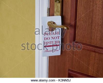A please do not disturb sign hanging on a brass door handle on a hotel bedroom door - Stock Photo