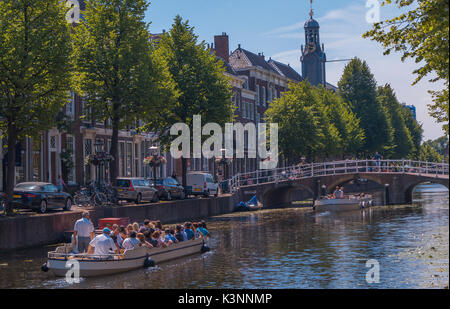 A tour boat going through the canal in Leiden, The Netherlands at the Steenschuur, Rapenburg with the sun shining - Stock Photo