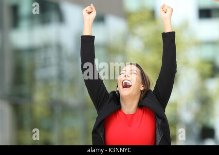 Single excited executive raising arms after success on the street - Stock Photo