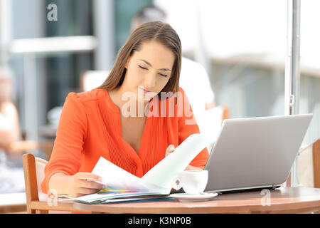 Single serious entrepreneur working reading documents sitting in a restaurant - Stock Photo