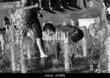 Manchester, United Kingdom - 15 August, 2017: Children playing at Piccadilly Gardens water fountains in Manchester - Stock Photo