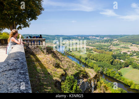 A young woman looks out over the Dordogne valley from Domme  in the Dordogne department in Nouvelle-Aquitaine in - Stock Photo