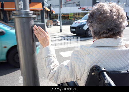 Disabled woman waiting in wheelchair at zebra crossing - Stock Photo