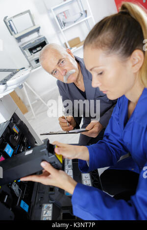 midsection of young businessman fixing cartridge in printer machine - Stock Photo