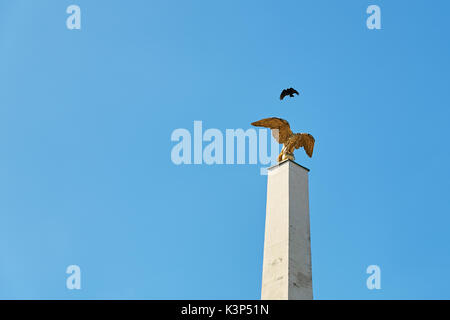 Vienna, Austria - September 24, 2014: Bird flies over a gilded eagle on a column at main gate of the Schonbrunn - Stock Photo