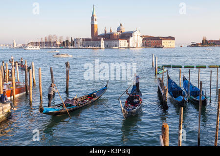 Two gondolas with tourists at sunset enterig Rio Palazzo o de Canonica, San Marco, Venice in front of the Doges - Stock Photo