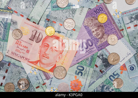 Singapore dollar and Coins on top of Malaysian Ringgit currency on pattern background, Malaysian Ringgit symbol - Stock Photo